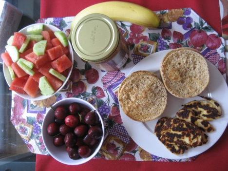 Clockwise from the top: banana, almond butter, 2 whole grain english muffins, fried Haloumi cheese, fresh cherries and raspberries, fresh watermelon and seedless cucumber